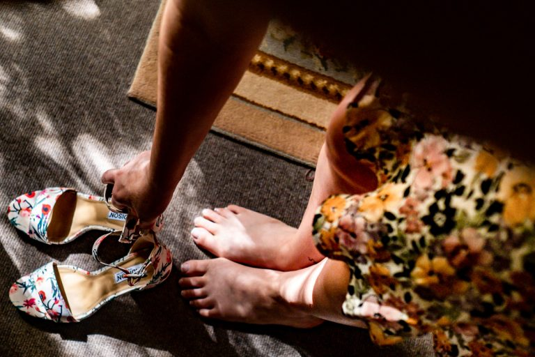 the light falls on the bride picking up her wedding shoes