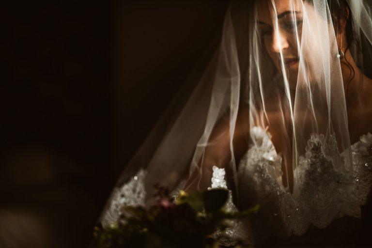 a soft portrait of the bride using natural light and her veil