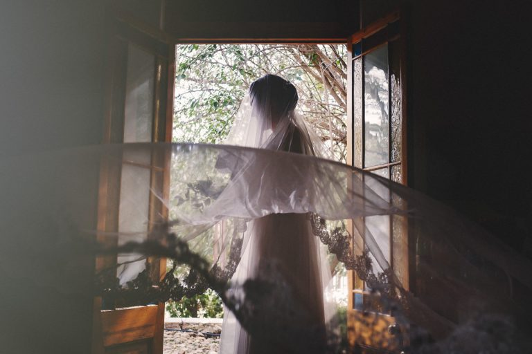 the bride stands in the door way for a wedding portrait with her veil