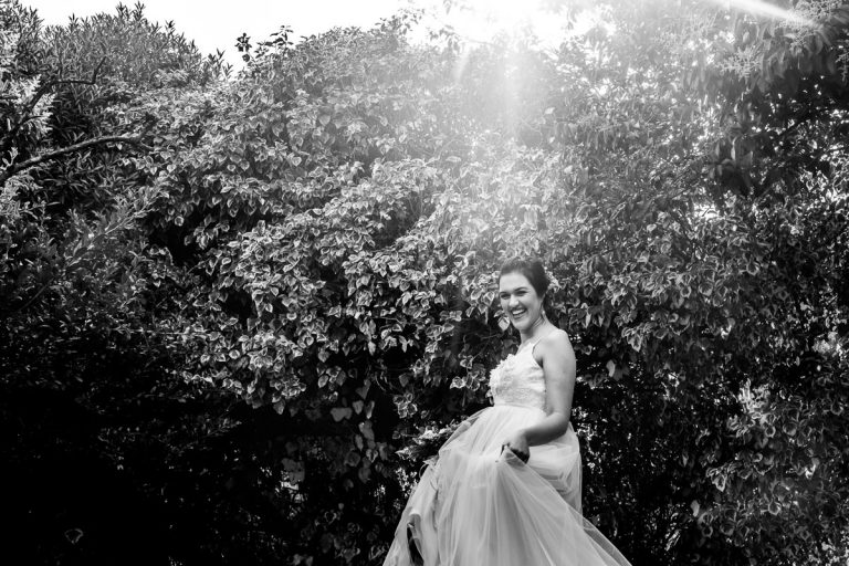 the bride plays with her beautiful wedding dress in the sun