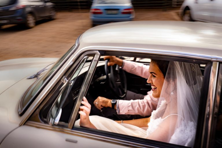 the happy bride in her vintage wedding car arrives at her wedding ceremony