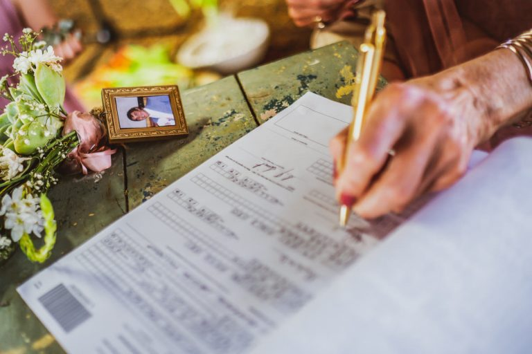 A Karoo Wedding where the mother of the bride signing the register with a photo of her late husband on the bride's bouquet