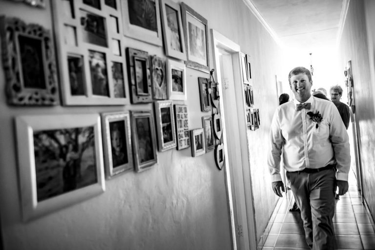 the groom walks down the corridor with old family photos up on the wall