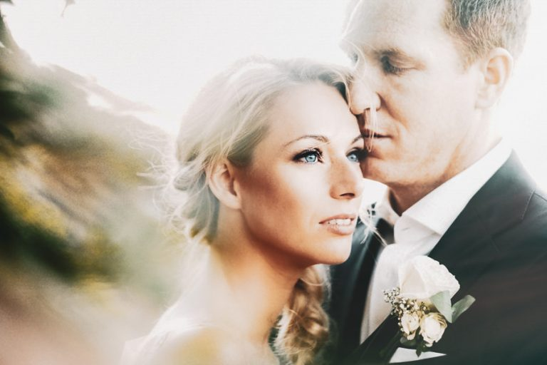 Beautiful Wedding Photos by Christelle Rall like this artistic fine art wedding portrait of the groom kissing his bride softly on the forehead.