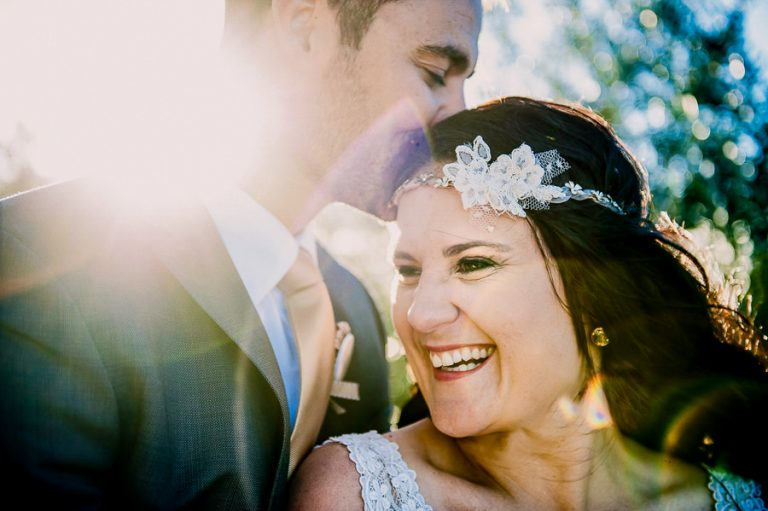 The groom gives the happy bride a loving kiss with filtering sunlight giving the image a magical touch.