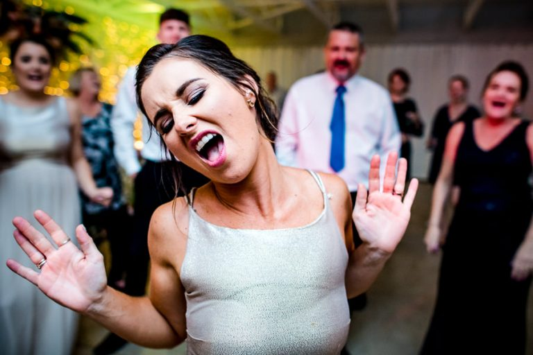 A dance floor reportage image of a bridesmaid doing a dance off.