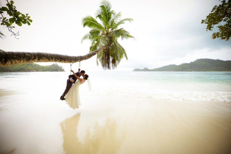 Beautiful Wedding Photos by Christelle Rall like this picture of the bride and groom on a beach swing that overhang on the ocean on the island of Mahe, Seychelles.