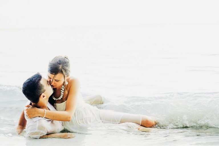A beach portrait of the bride and groom in the ocean on Dennis island, Seychelles