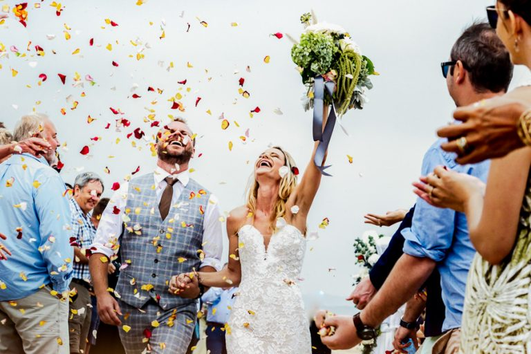 Beautiful Wedding Photos by Christellle Rall like this jubilant image of the bride and groom being tossed by rose petals just after their wedding ceremony.