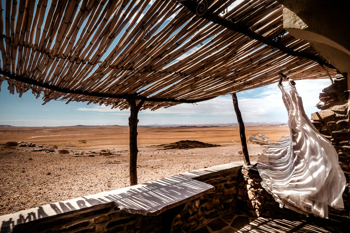South African Wedding Photographer, Christelle Rall took this photo of a wedding dress flapping in the wind on a veranda with the Namibia desert in the background
