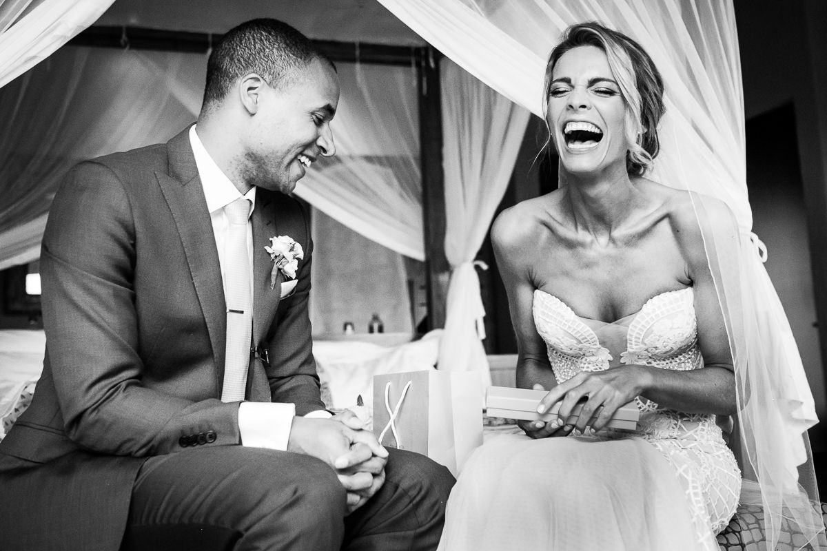 South African Wedding Photographer, Christelle Rall took this picture of the bride laughing happily as she is opening a gift from her husband.