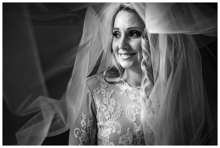a creative bridal portrait of the bride with her vail