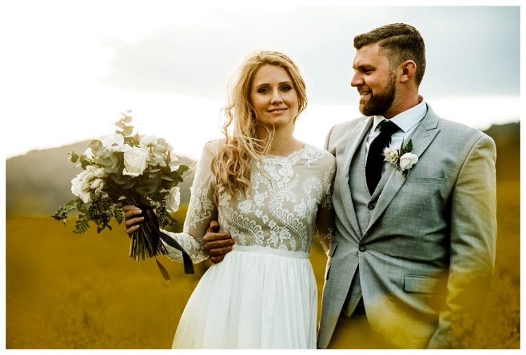 the groom looks lovingly at this wife in the yellow canola fields