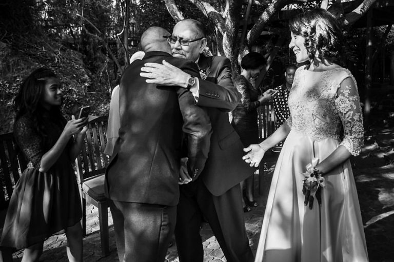 the father of the bride hugs her fiance at the end of the isle