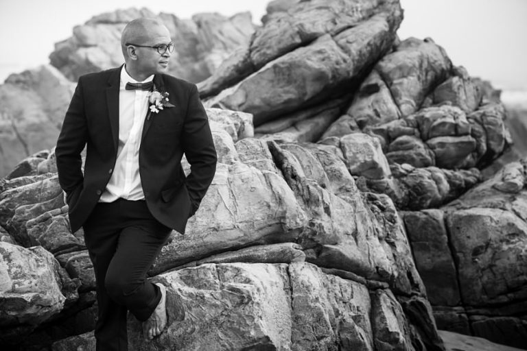 a black and white groom portrait on the beach