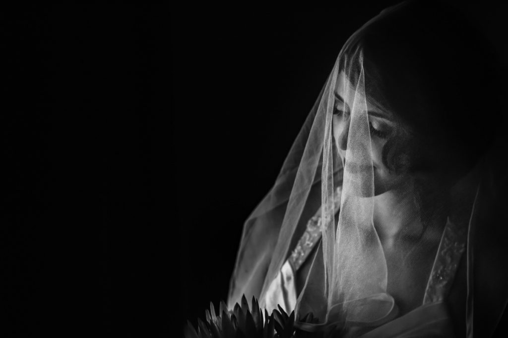 An artistic black and white portrait of the bride with her veil