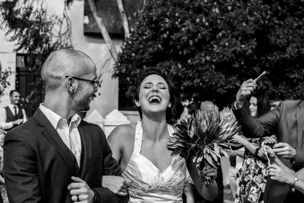 the bride and groom enjoys walking through the line of guests as they blow bubbles at them