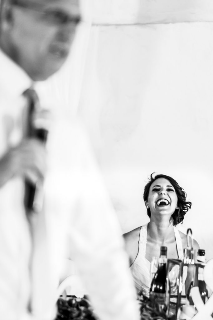 the bride laughs at a joke her father made during his father of the bride wedding speech