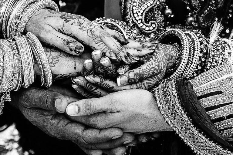 a close up photo of the hands from a Hindu wedding
