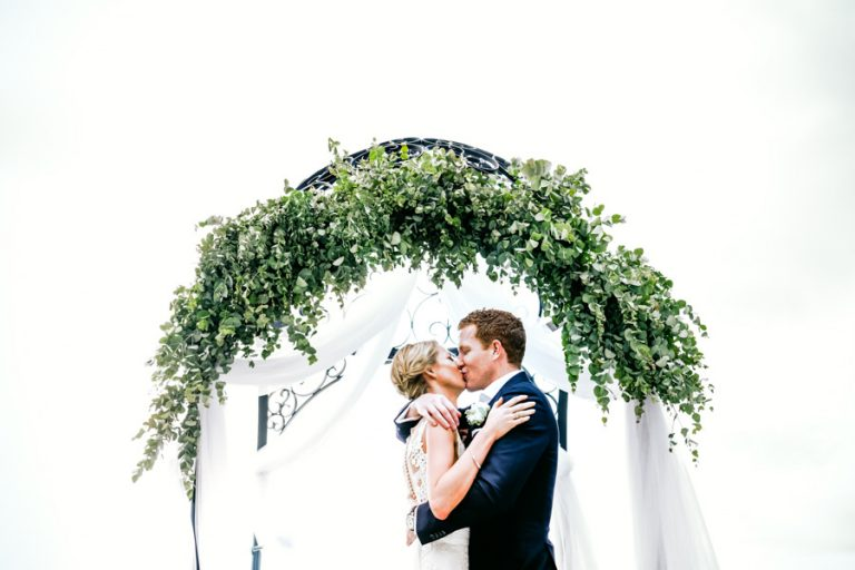 a bride and groom kiss as husband and wife