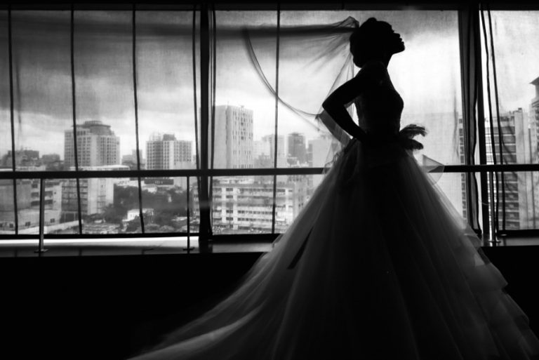 a silhouette portrait of a bride with Luanda's city in the background