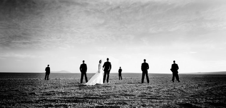 the bride with the groomsmen in an open field