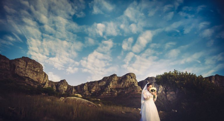 a bride smelling her bouquet with the clouds and mountains in the background
