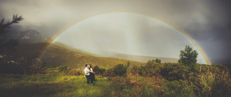 an engagement photo with a full rainbow in the mountains