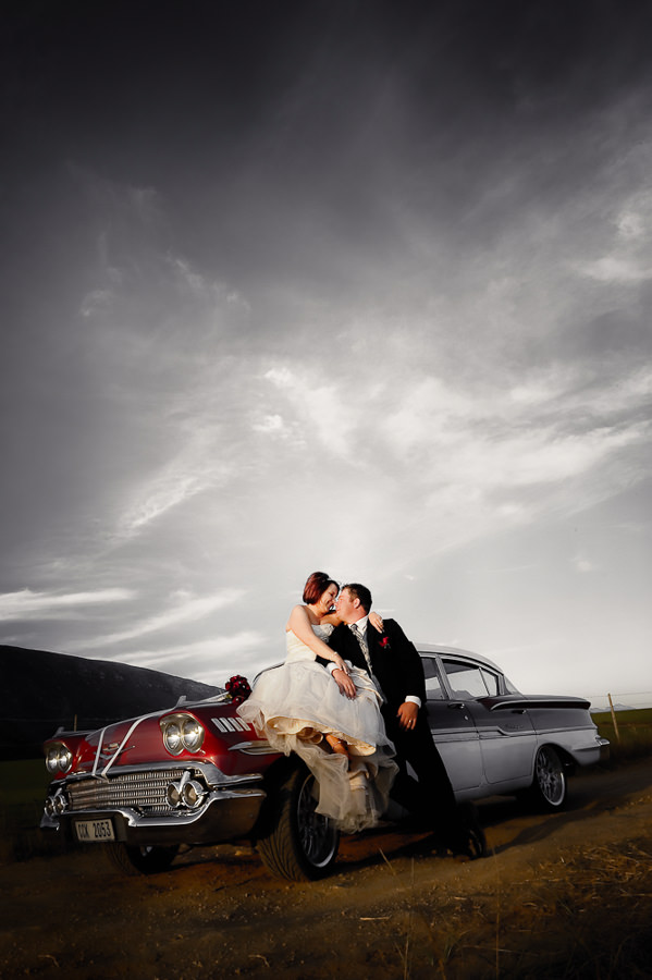 a loving moment between the bridal couple with a vintage car