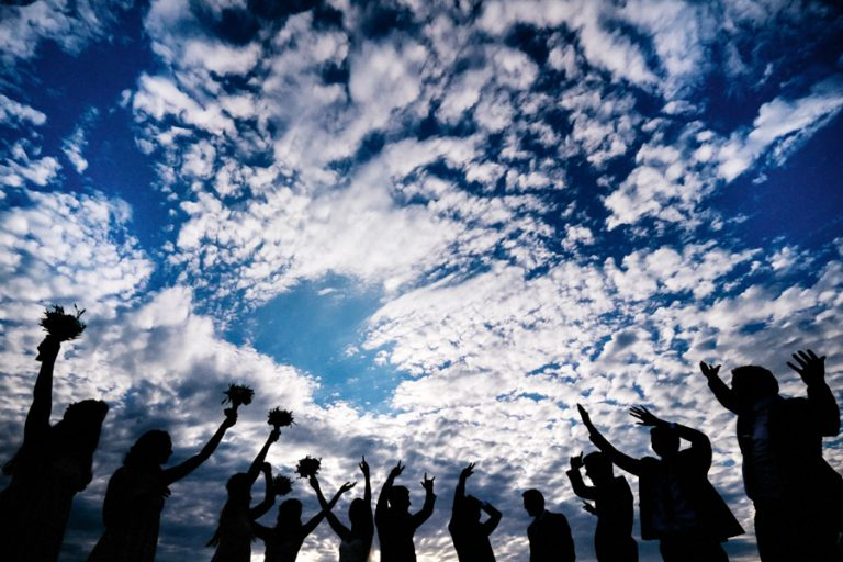 a silhouette of the bridal party with clouds