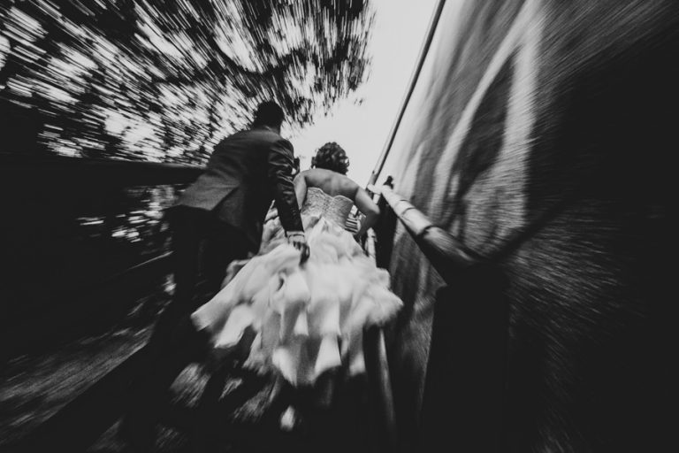 a creative photo of the bride and groom walking up the stairs