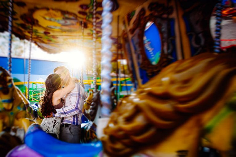 an engagement photo of the couple kissing on a carousel