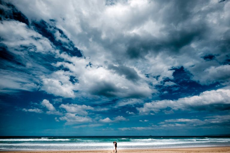 a wide shot of a bride and groom with a wide open beach and clouds