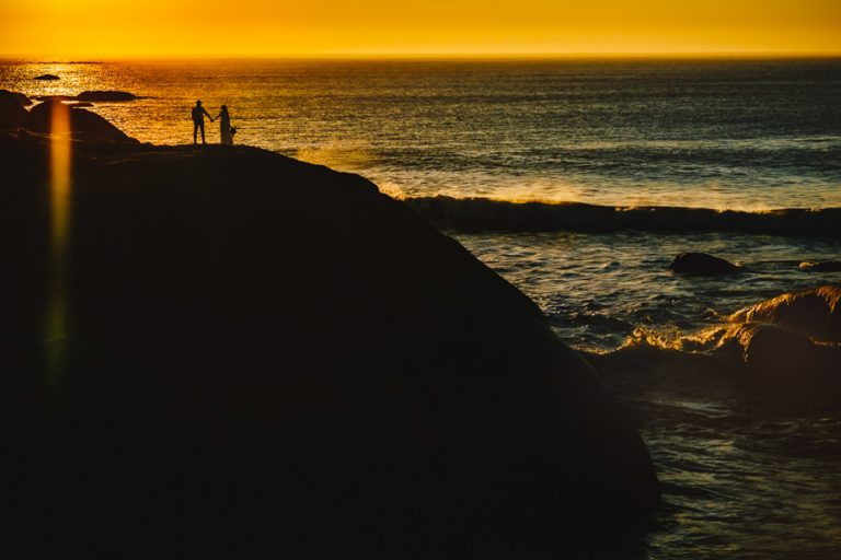a silhouette photo of the bride and groom on a cliff overlooking the ocean