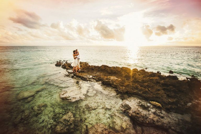 a bridal couple at the end of Denis island in Seychelles with the sun rising