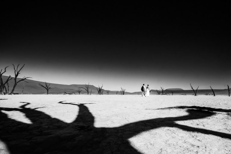the bride and groom walk amongst the dead trees at Sossuvlei, Namibia