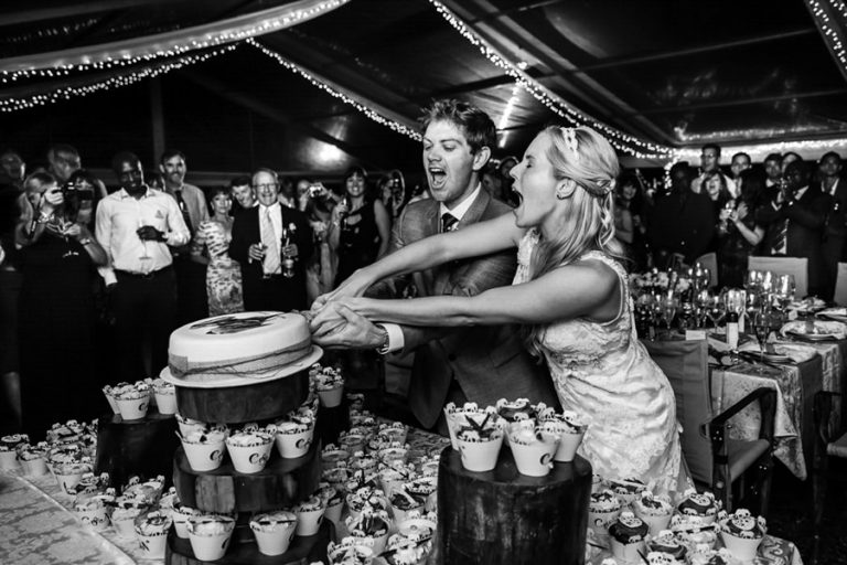 the newlyweds having a blast while cutting the cake