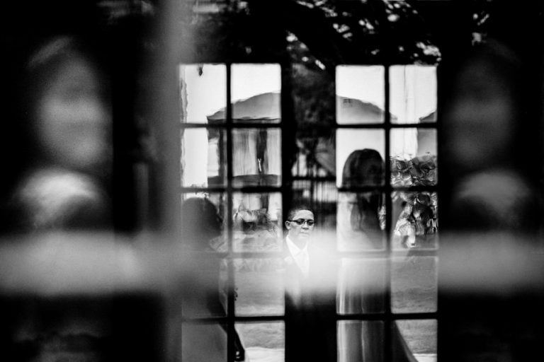 a black and white reflection photo of the groom