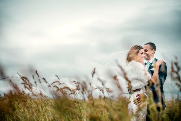 a romantic photo of the newlyweds in the field with thunderstorm weather