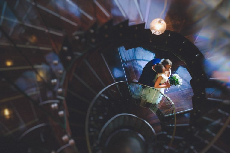 the couple embrace on a swirling stairs