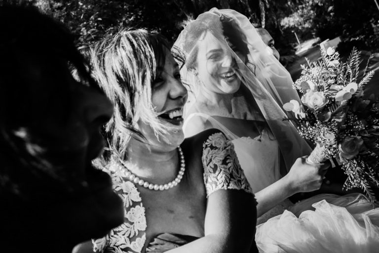 the bride laughs as they ride to the wedding ceremony