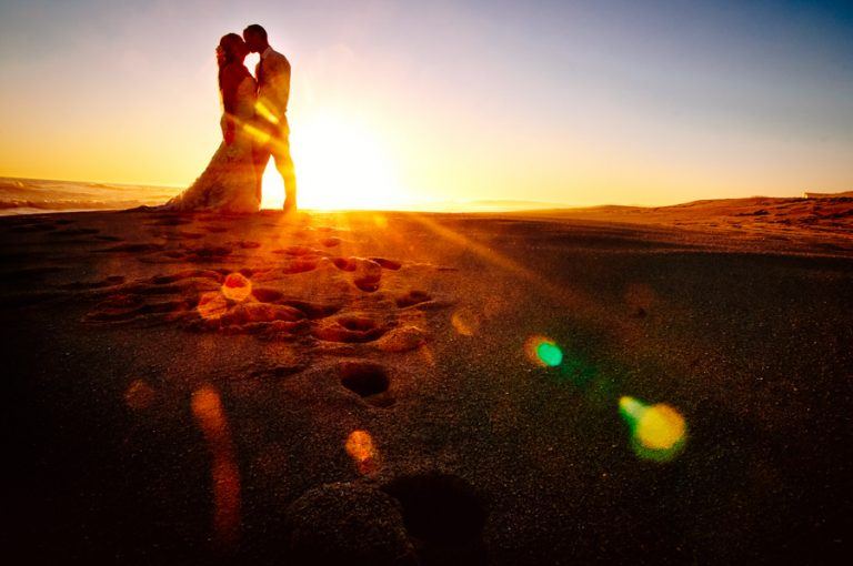 a silhouette photo of the bridal couple kissing on the beach