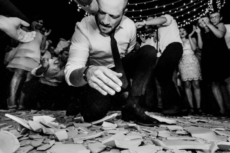 a wedding guest dance on the broken plates at this Greek wedding