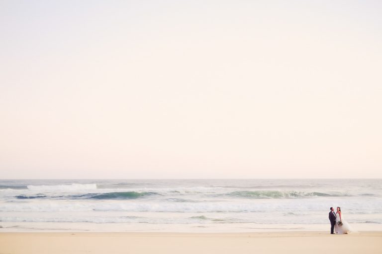 a wide shot of a bridal couple on an empty beach