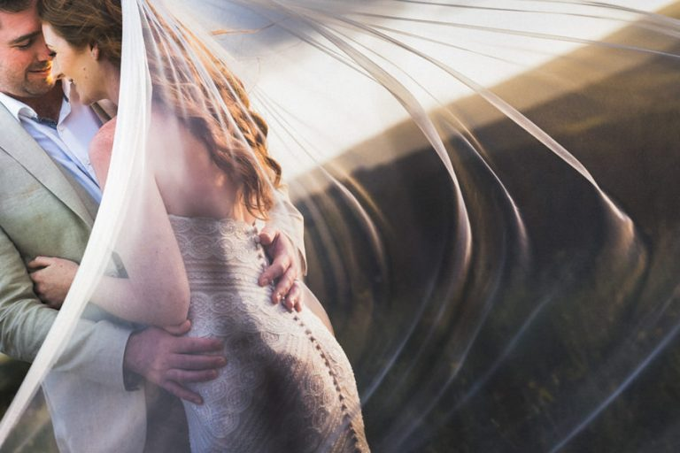a romantic photo of the newly weds using the wind and veil