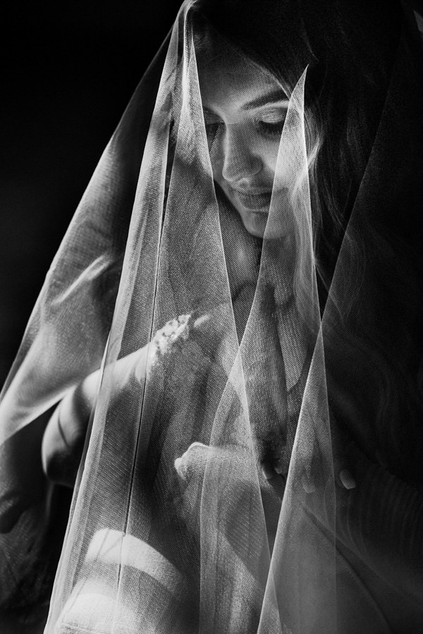 a creative portrait of the bride using her veil