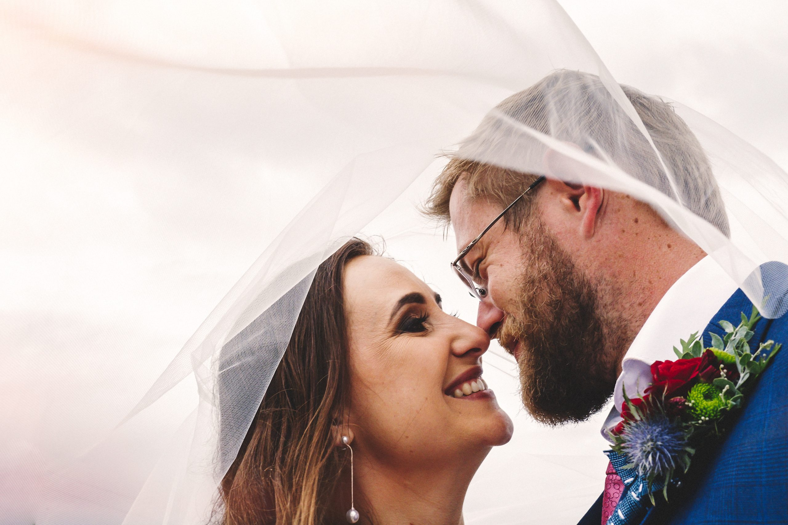 a photo of a happy couple using a veil
