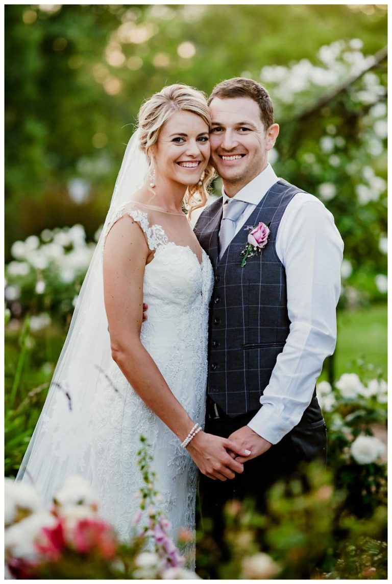 a classical photo of the bride and groom in the gardens