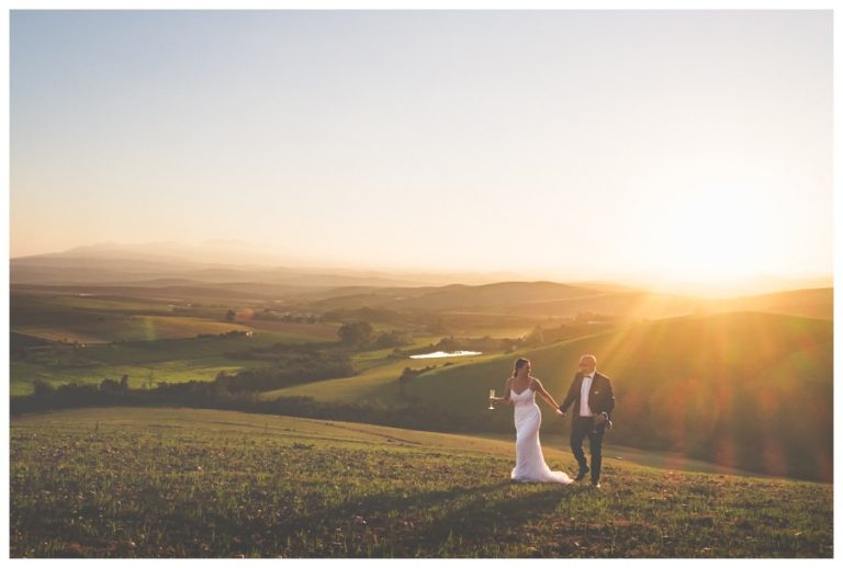 the bride and groom walking in the field with the sun setting behind them