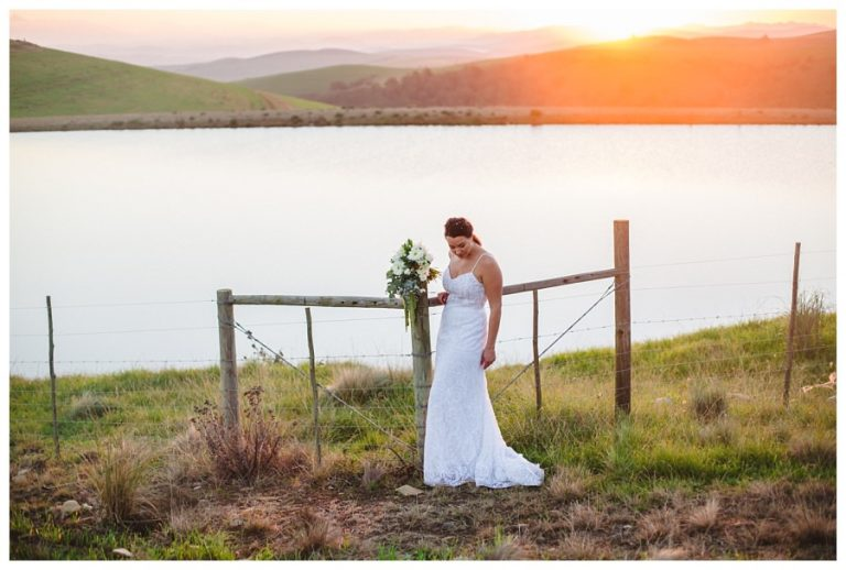 the bride next to a dam with the sun setting in the background